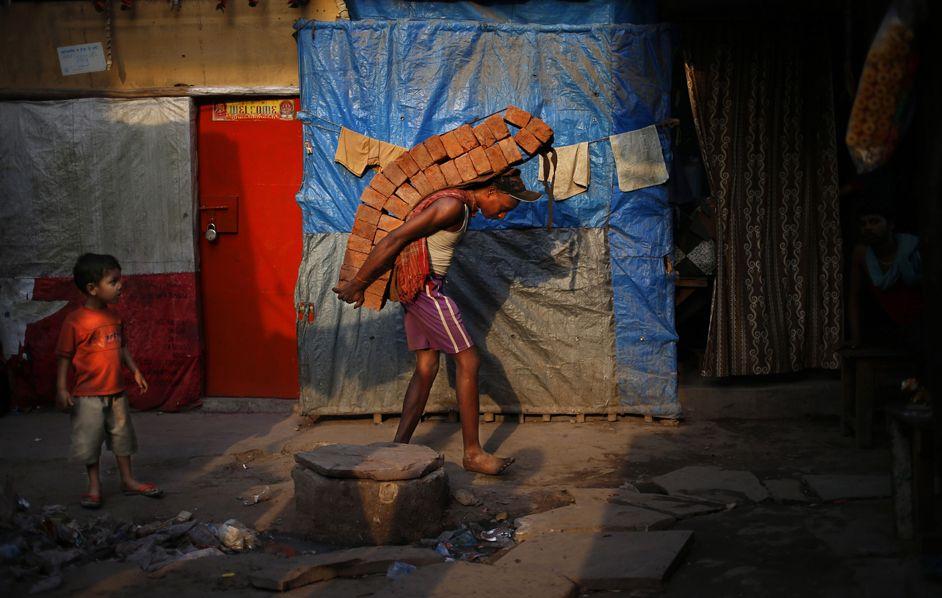 Un lavoratore ripara una casa danneggiata a New Delhi, in India. (Saurabh Das, Ap/Lapresse)