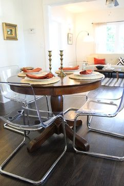 clear acrylic dining chairs paired with traditional pedestal table