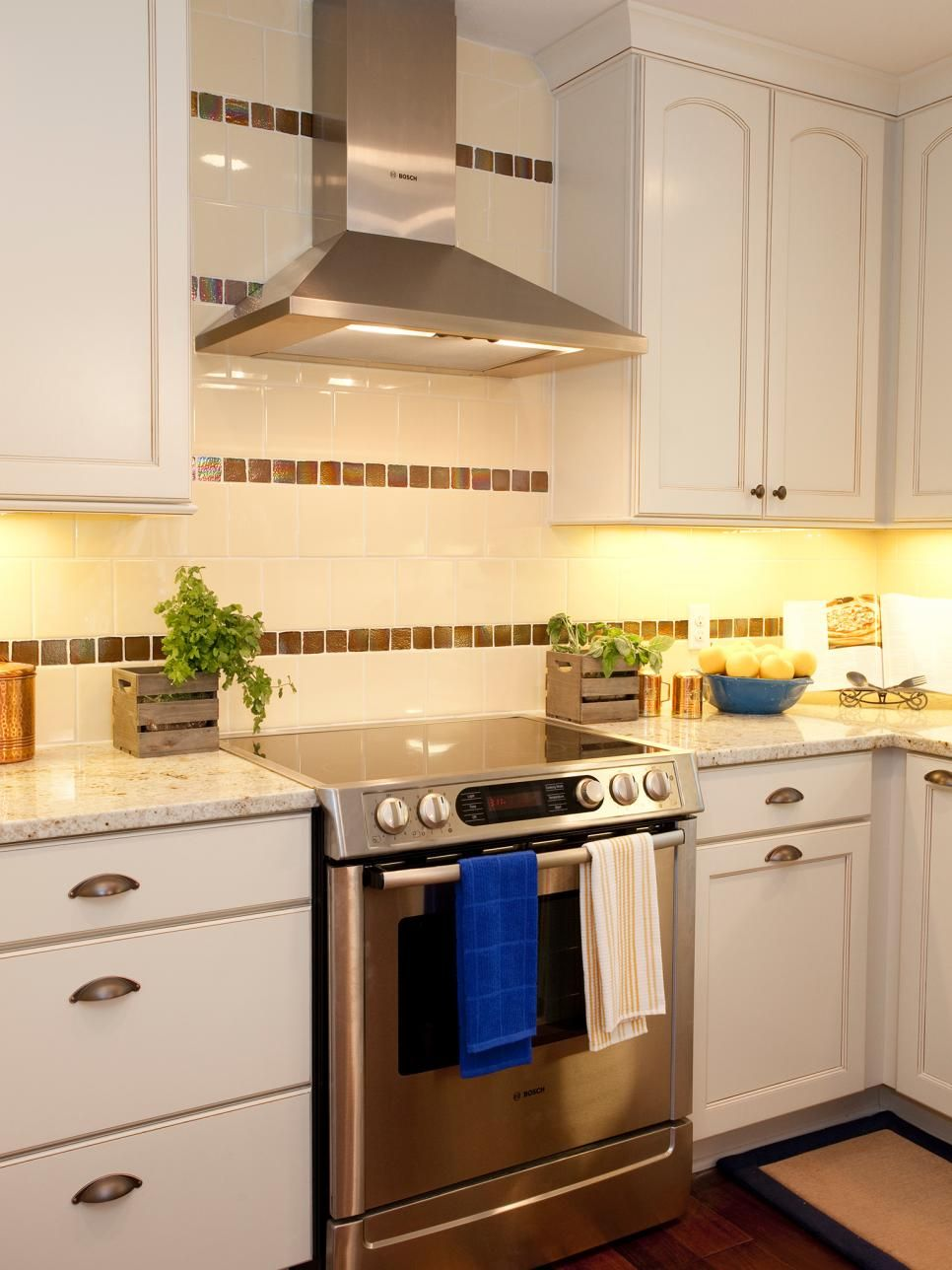 A White And Brown Striped Tile Backsplash Extends To The Ceiling Behind The Stainless Steel Range