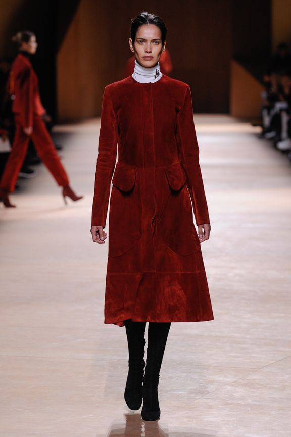 Riding spirit coat in brick red full grain calfskin, high waisted tapered trousers in blue-black wool gabardine, brooch in rainbow jasper and dumortierite #hermes #hermesfemme #womenswear #fashion