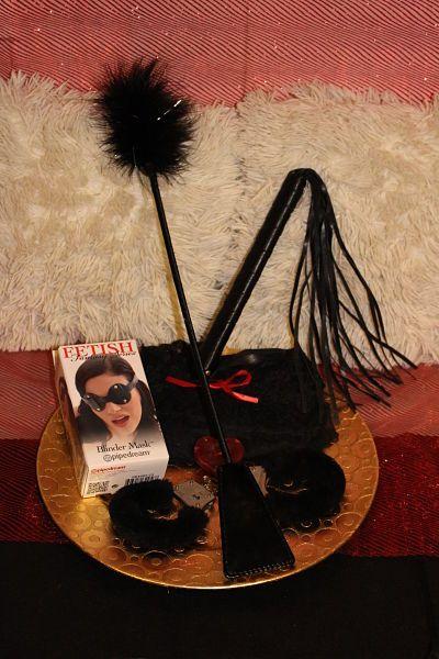 CESTA 7; 50 SOMBRAS Fusta Estimuladora con pluma negra, acompañado de las esposas el picardías y como no puede faltar la seductora mascara y el preservativo, acompañado todo por un seductor y sensual latigo para volverlas locas, por 105€
