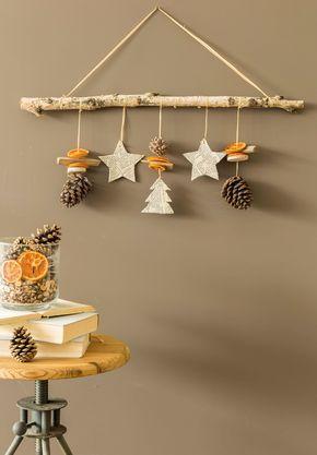DIY Suspension de Noël par Rose & Bergamote (artisan fleuriste à Haubourdin). Matériel nécessaire : 1 branche de bouleau ou autre variété d'environ 70 cm, du rafia ou de la ficelle (environ 1,30 m), 3 ou 4 pommes de pin, rondelles d'orange séchée, du carton, un vieux livre, vernis colle, rondelles de branche, morceaux de bois, ciseaux. Retrouvez toutes les explications page 8 de notre Pop Magazine de décembre (#13)