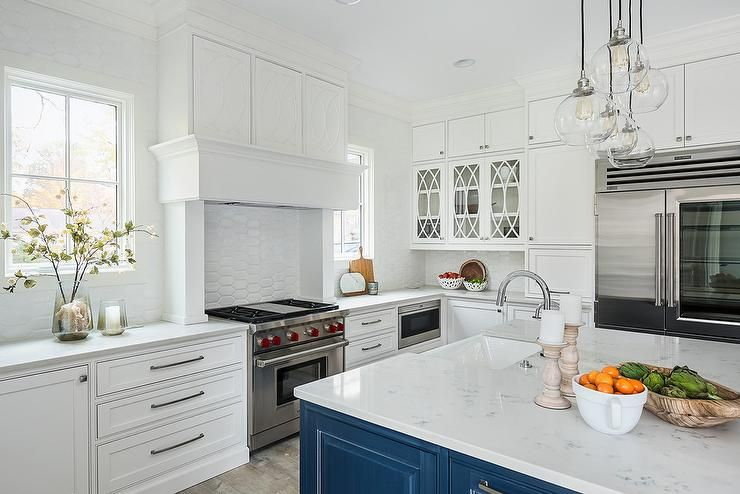 Windows framed by white oval backsplash tiles flank a ...