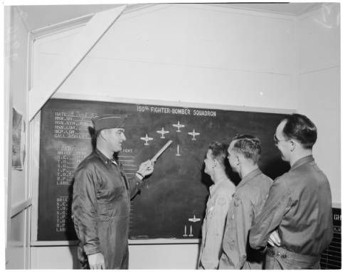 Lt. Col. Martin H. Johnson, 34, Commanding Officer, 190th Fighter-Bomber Sqd., George Air Force Base, Victorville, conducts pre-flight briefing. Others, l to r: are 1st Lt. Orlando Dalke, 28; Capt. Wm. R. Sproat, 30; and 1st Lt. Albert P. Winkleman, 30. All are National Guard flyers from Boise, Idaho.   Victorville layout, 1952 :: Los Angeles Examiner Collection, 1920-1961