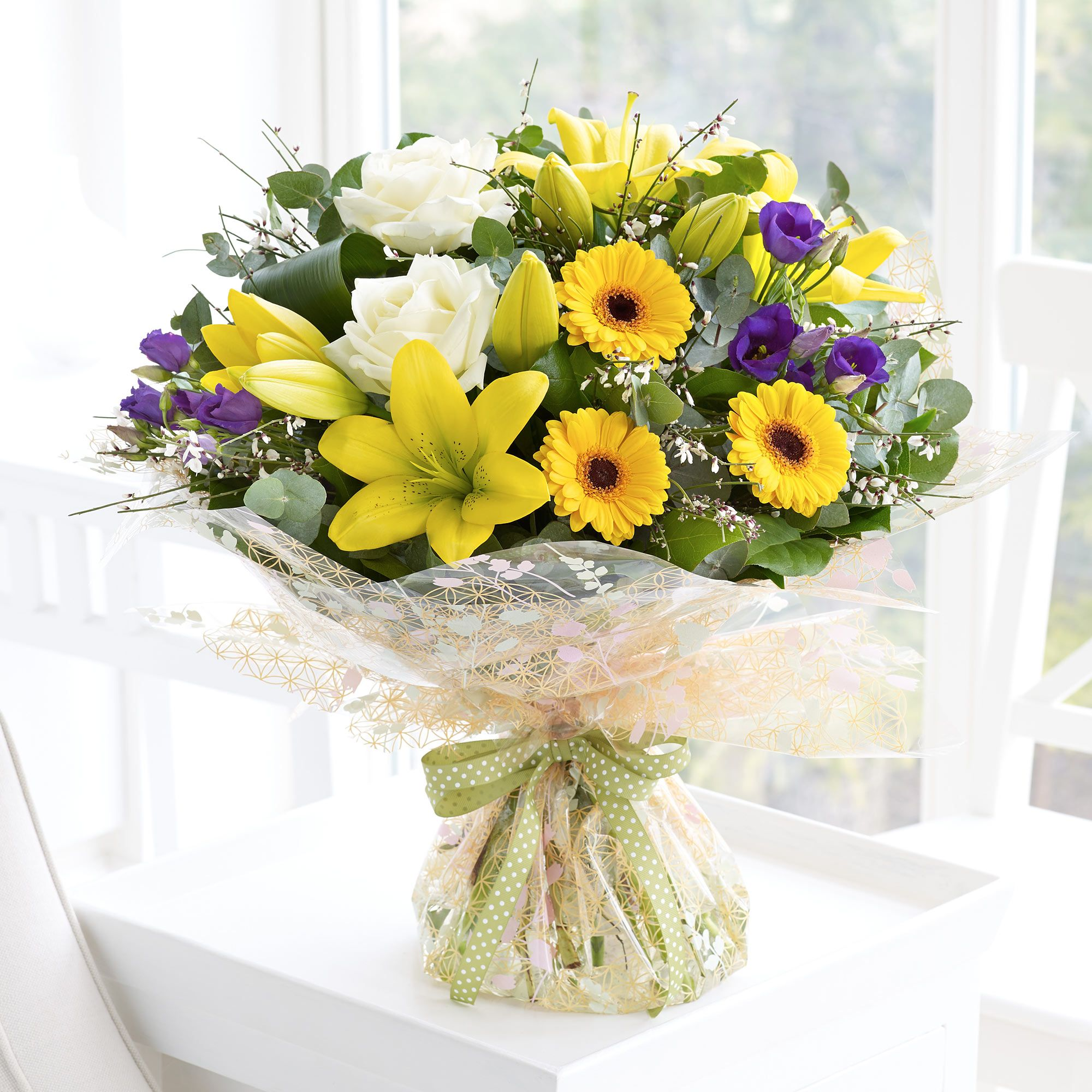 Featuring purple lisianthus, white roses, yellow lilies