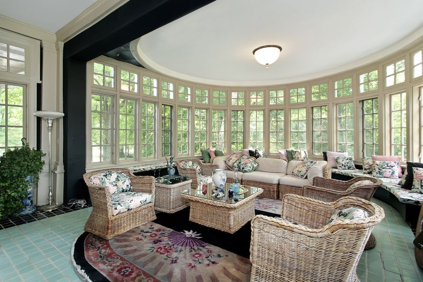 Solarium-style living room with semi-circular ornate bay window. Wicker  furniture throughout