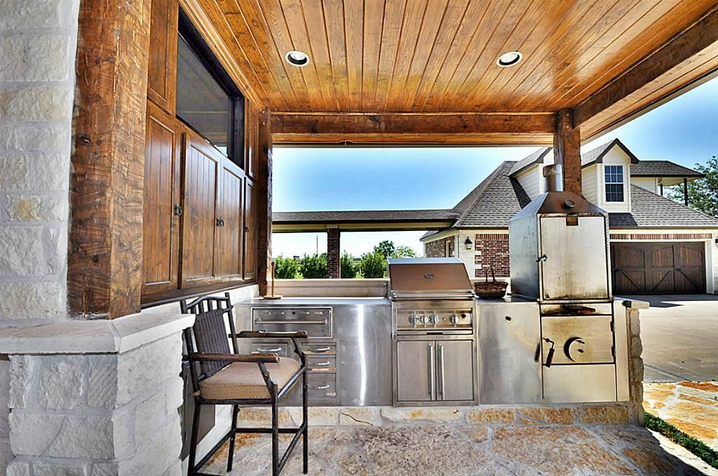 a close up view of the outdoor kitchen complete with stainless steel grill smoker and warming on outdoor kitchen with smoker id=76454