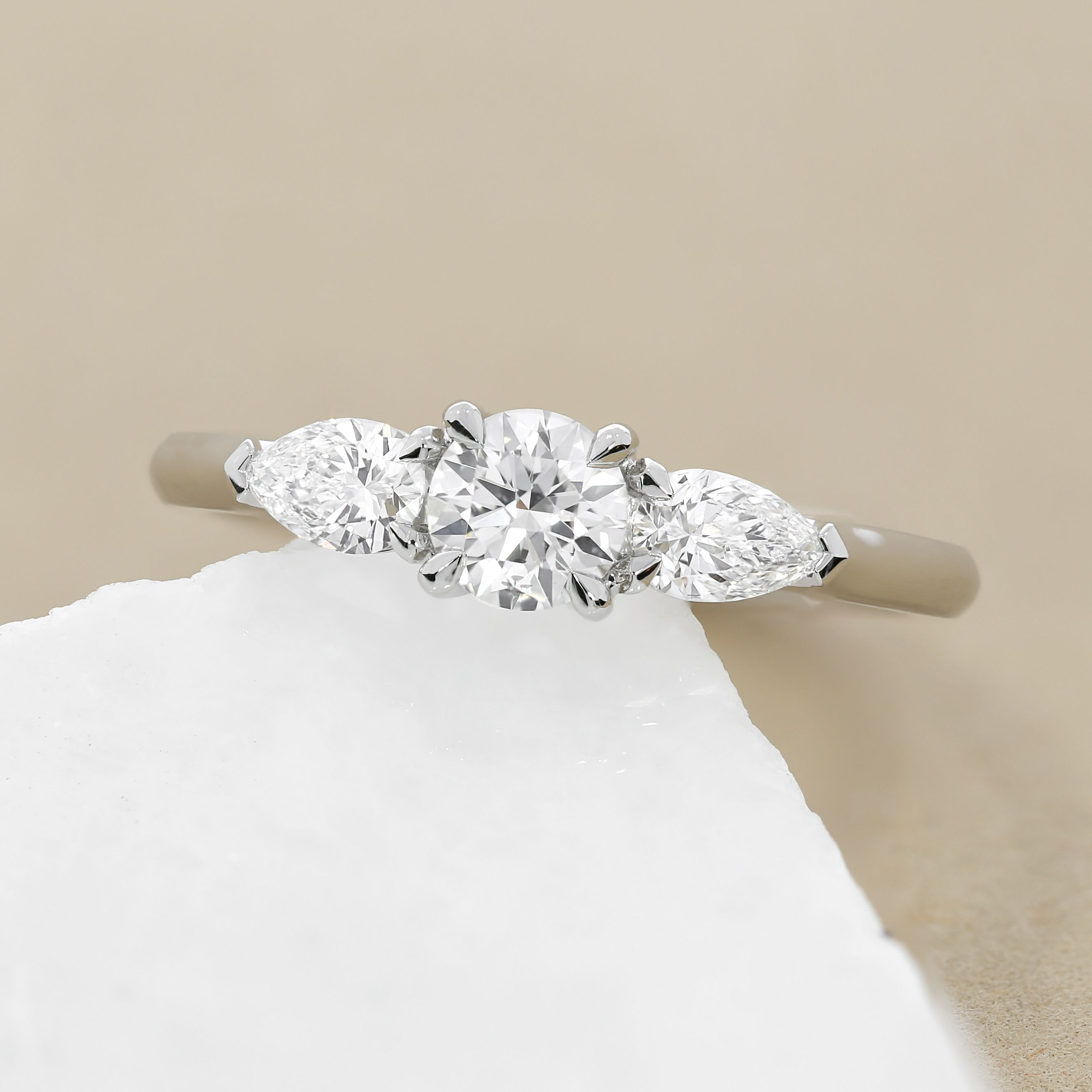 This three stone engagement ring features a round