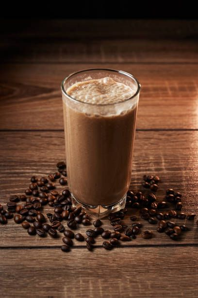 coffee and banana smoothie in a glass on a wooden background