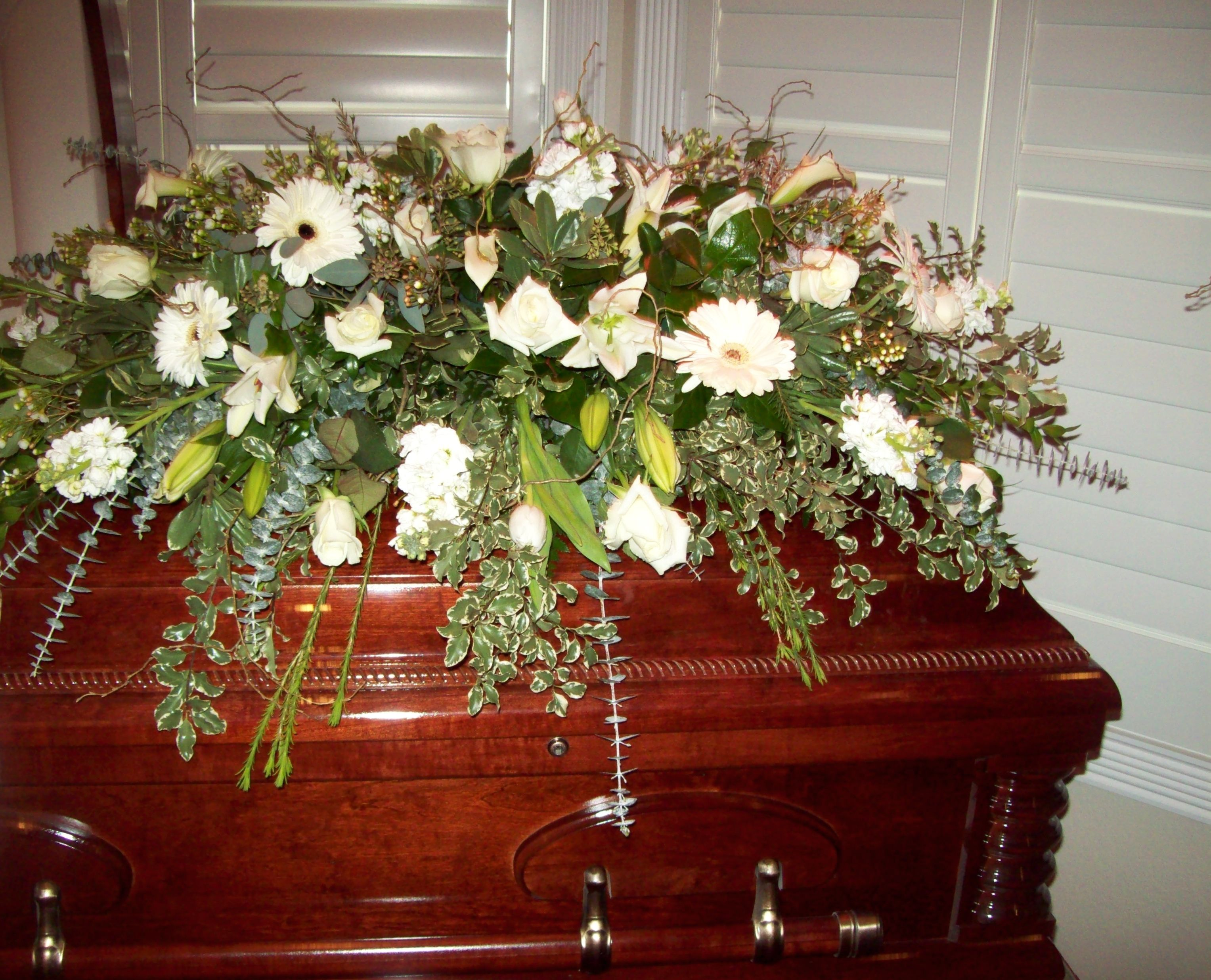 Premium white flowers with mix of natural greens complement this premium white flowers with mix of natural greens complement this wooden casket appropriate for a izmirmasajfo