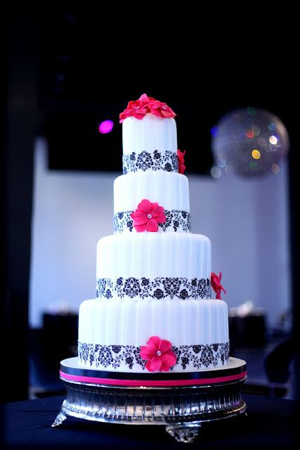 A pleated 4 tier cake with a black floral font ribbon and hot pink flower accents  The Grand Wedding 2011  Photo Credit: Impressions Photography  Cake: Kakes by Karen  Wedding Styling  Planning: Weddings by Socialites