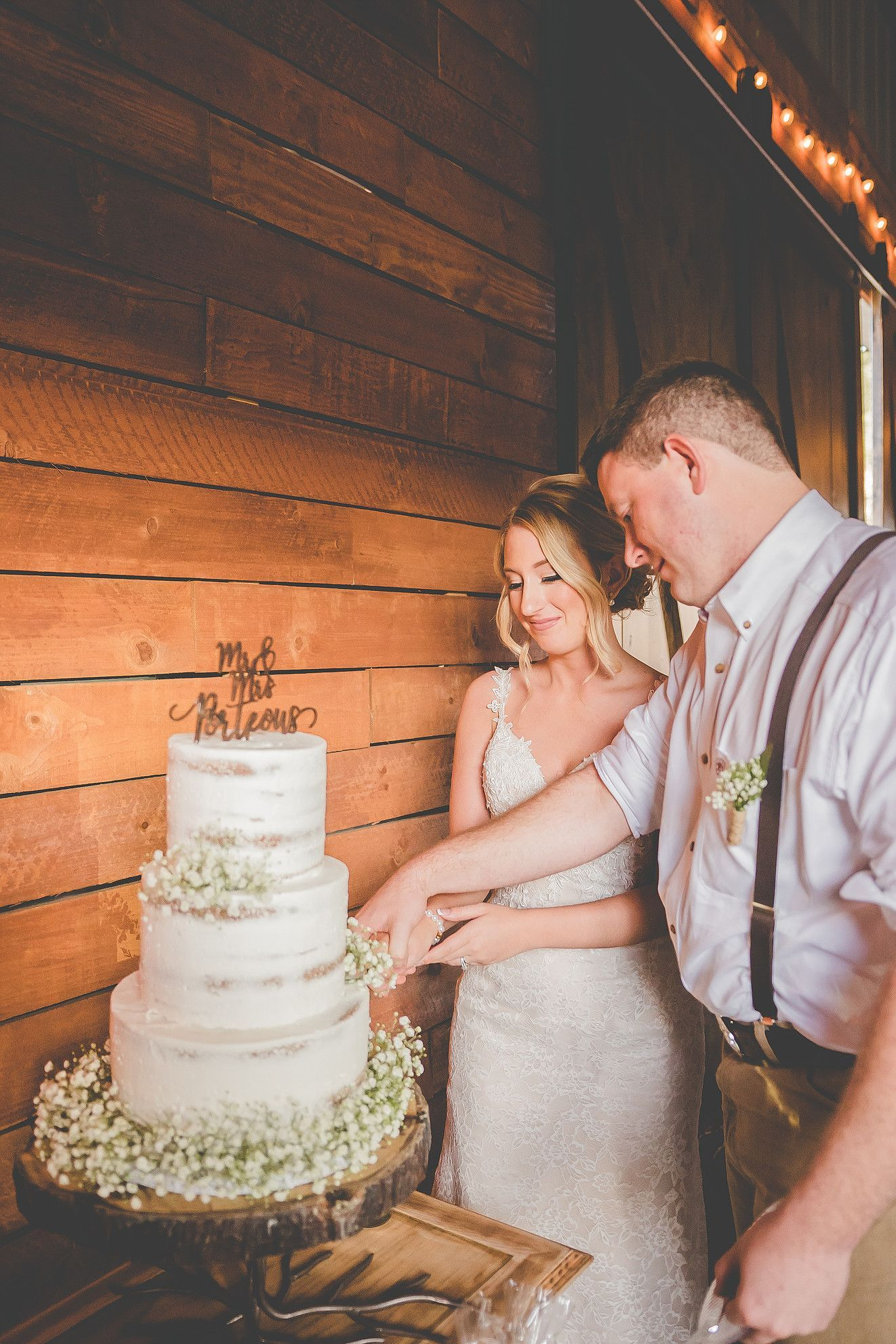 Bare wedding cake with babyus breath wooden cake topper and cut