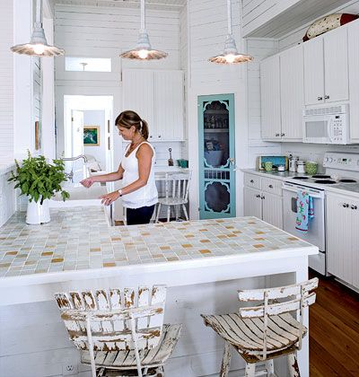 Love the pantry screen door. White kitchen in beach home on Little Tybee Island in Georgia with glass-tile countertops and a screened door to the pantry