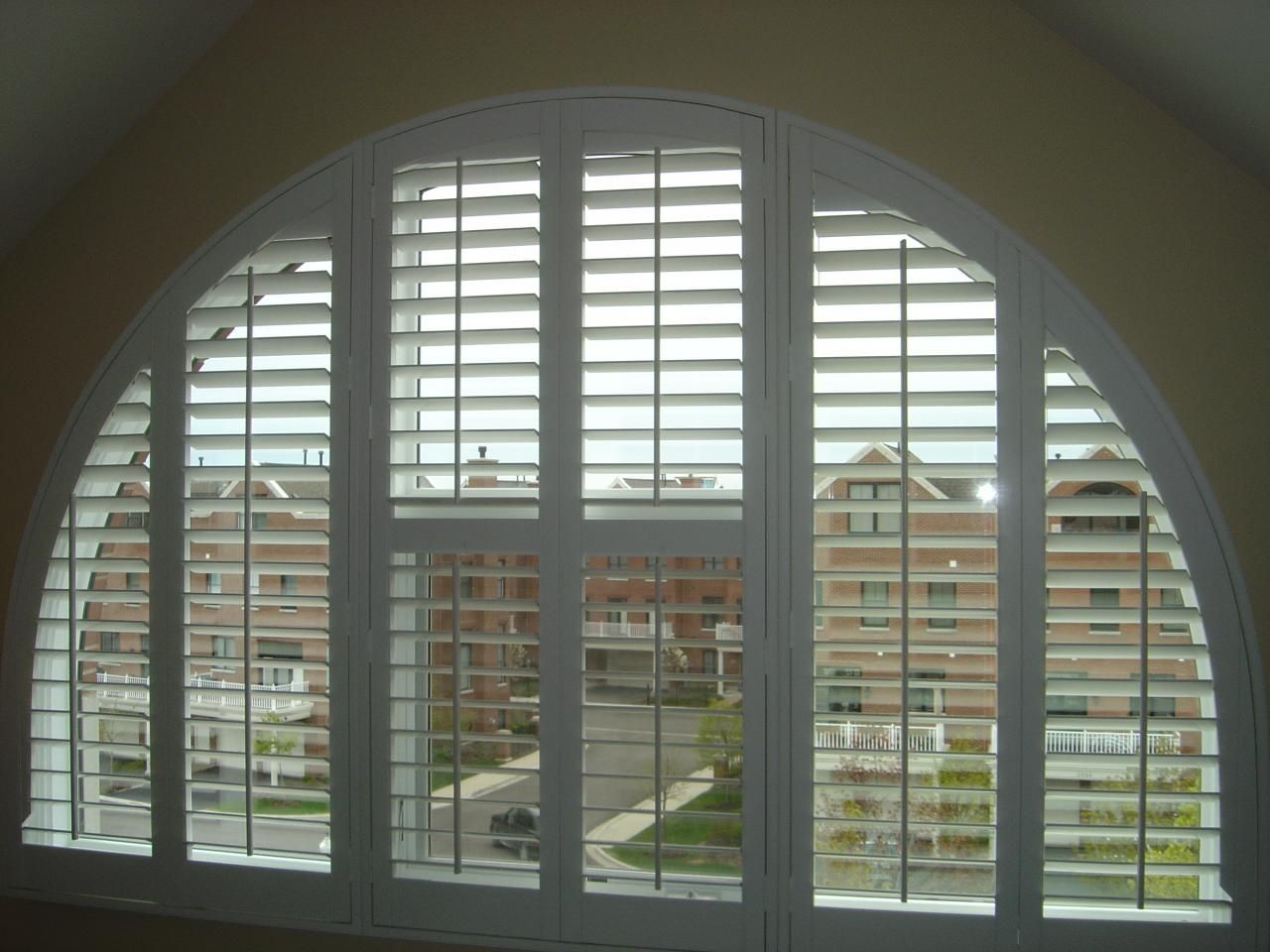 This Arched Window Is Adorned With White Plantation Shutters It Is A Unique Window Treatment In