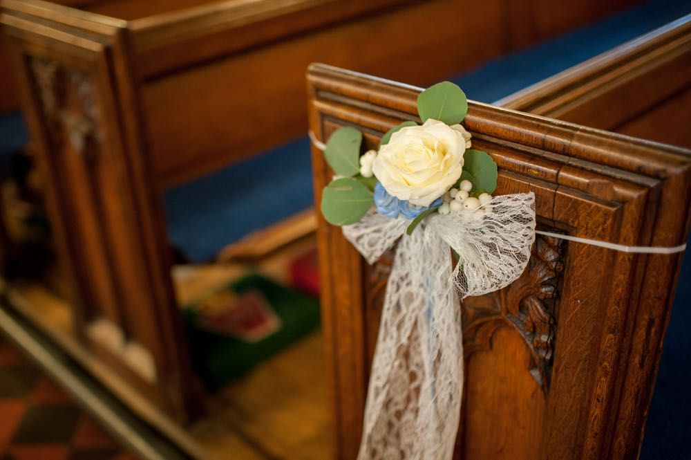 Small cluster of flowers displayed on the pew ends with a lace bow - Flowers by Laurel Weddings - Image by Zen Photographic