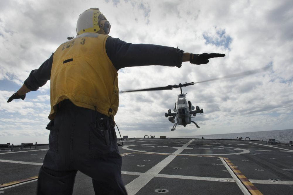 Boatswain's Mate 2nd Class Adam Garnett from Anchorage, Alaska, signals an AH-1 Cobra helicopter from Marine Air Group (MAG) 24 during deck landing qualification training aboard the littoral combat ship USS Fort Worth (LCS 3). Fort Worth departed its home port of San Diego Nov. 17 for a 16-month rotational deployment to Southeast Asia in support of the Navy's strategic rebalance to the Pacific. (U.S. Navy photo by Mass Communication Specialist 2nd Class Antonio P. Turretto Ramos)