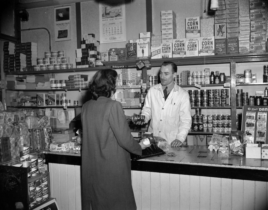 Woman Being Helped By A Grocery Store Clerk, 1940s (Photo