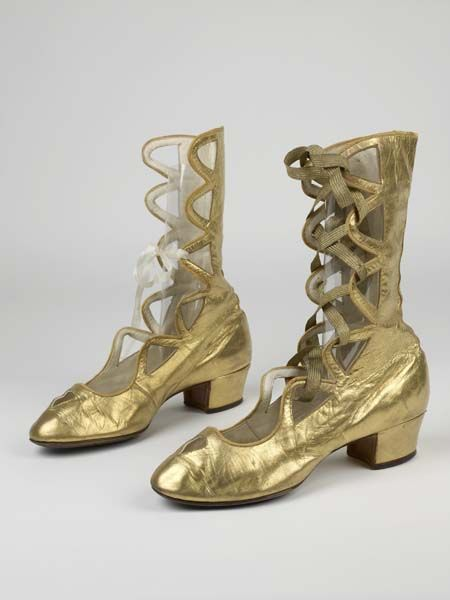 Gold kid leather heeled open boots worn by Anna Pavlova in 'Gavotte Pavlova', 1913. Mid-calf length with cut-out scallop loops for ribbon ties.