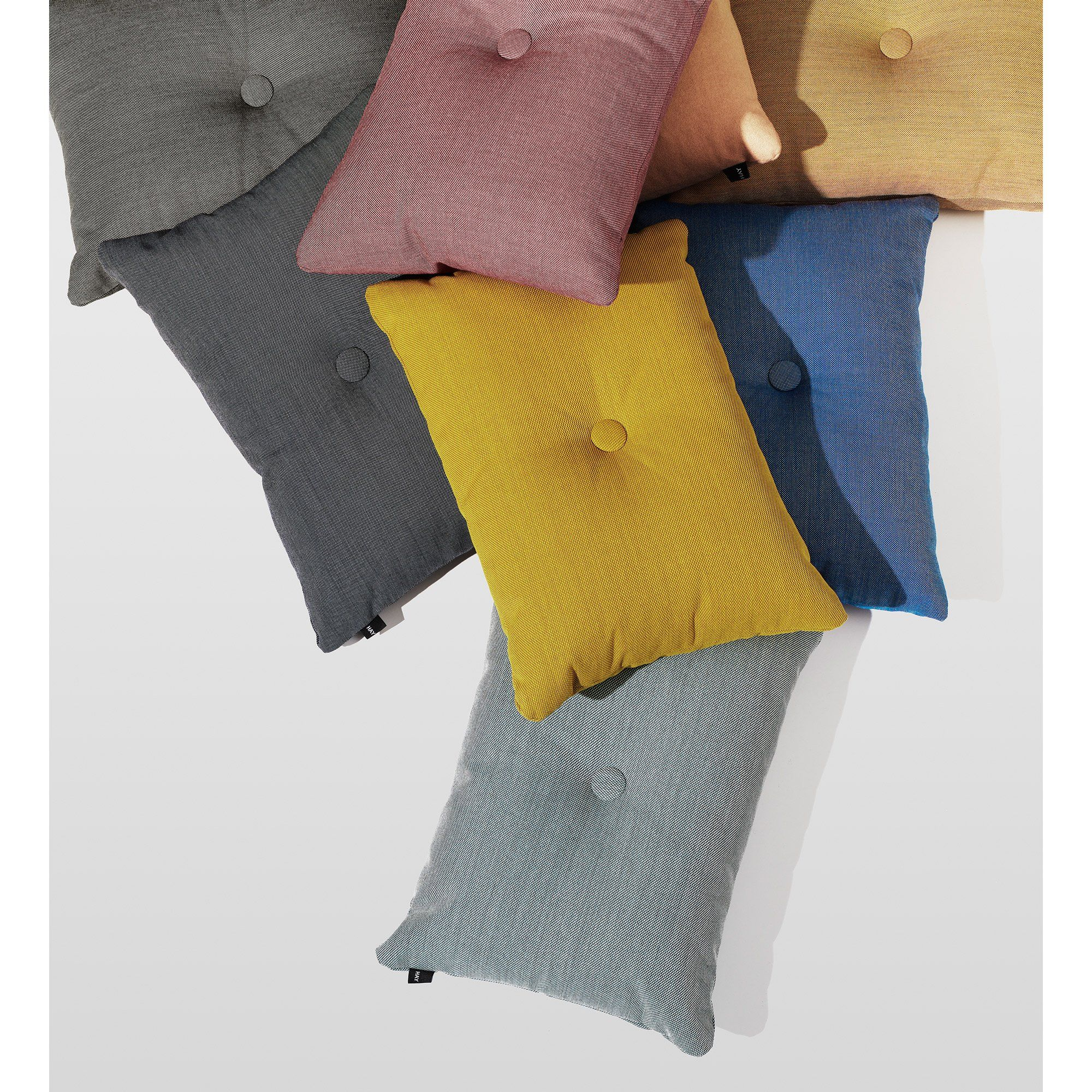 Dot is HAY's simple and distinctive cushion made in Steelcut trio, Surface or Soft velvet fabric. Dot has one covered buttons in contrasting colours on its belly.