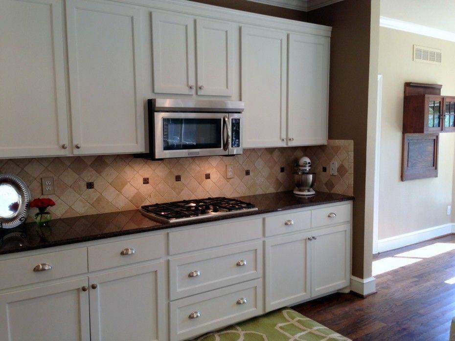 Travertine backsplash with white cabinets and black countertops ...