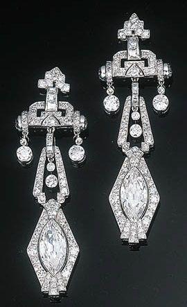 A Pair of Art Deco Diamond Ear Pendants. Each comprising a marquise-cut diamond within a circular-cut diamond frame suspended from a diamond-set geometric surmount and diamond collet, circa 1930.
