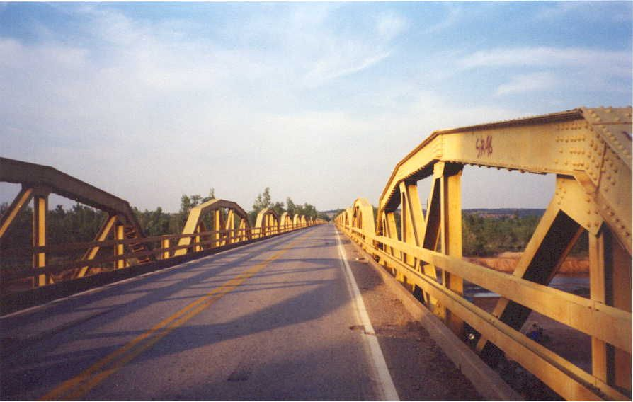 This old Route 66 bridge spans the South Canadian River, which at this point is the boundary between Canadian and Caddo Counties in Oklahoma. It is 3,944.33 feet in length and was built jointly by the state and federal governments. Contract for its construction was awarded on August 2, 1932. It was completed and accepted by the state on July 1, 1933. It consists of 38 standard design 100-foot pony truss bridges and two 40-foot approaches.