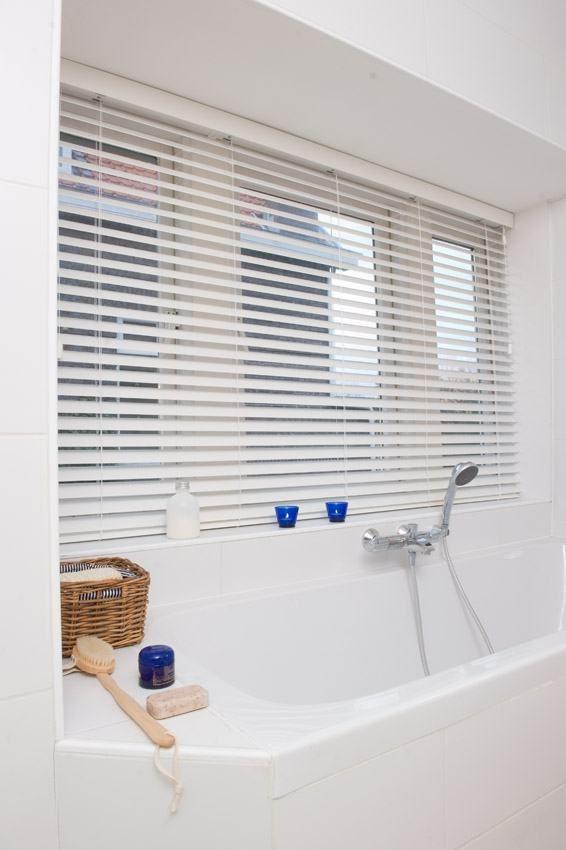 Geopende witte houtlook PVC jaloezieën in een badkamer | Badkamer ...