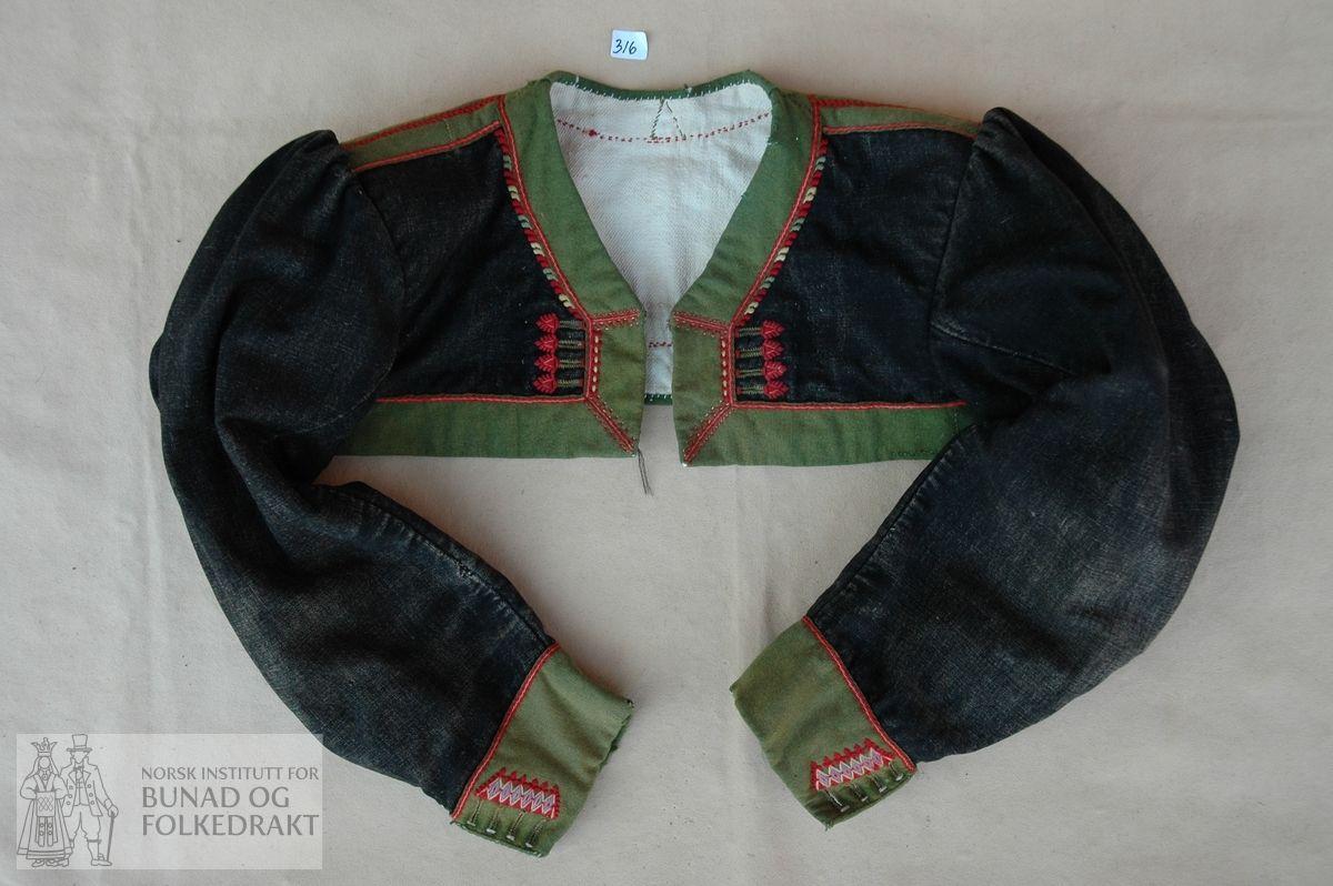 """Trøye med skulder -og sidesaum og falske panelsaumar på ryggen. Svart kledesliknande tøy (ser kanskje ut som det kan vere bomull renning med ull innslag). Veldig slitt. Fora med kypertvove bomull, påsydd """"oppstiving"""" av vadmål rundt erme. Brei kant av grønt klede pryda med """"løyesaum"""" langs nedkant, framkant og hals, over skuldersaum og panelsaum i ryggen. """"Løyesaum"""" og 4 knapphol på kvart framstykke.   To-saumserme med rynka ermtopp, fora med kypertvove bomull. Belegg av grønt klede framme…"""