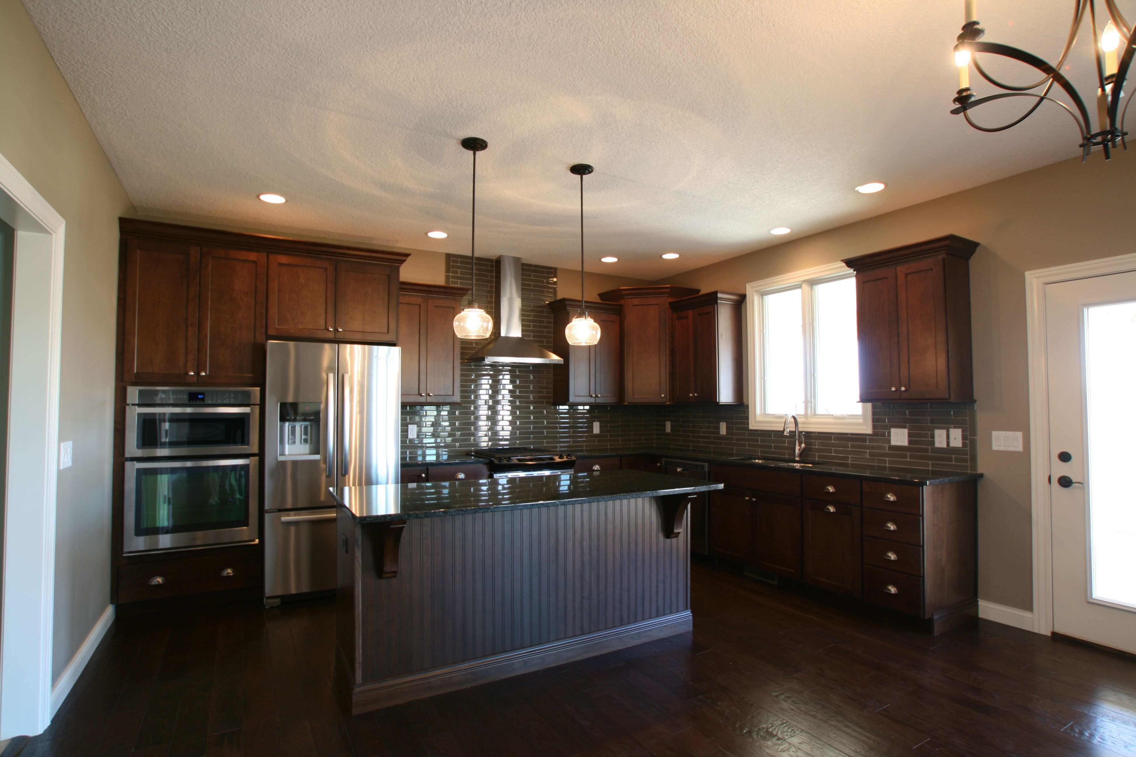 cabinets stretch all the way to the ceiling in this transitional kitchen glasstile installed on kitchen cabinets to the ceiling id=70605