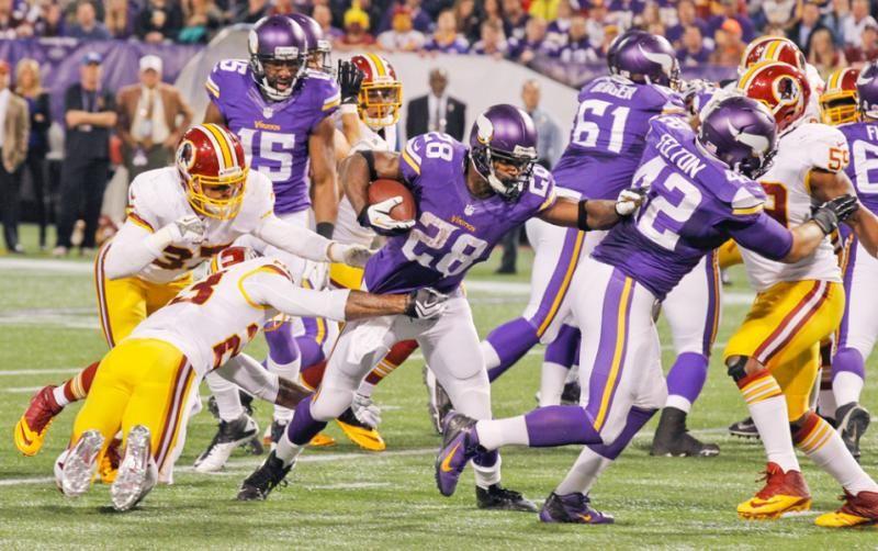 Vikings running back Adrian Peterson (28) tries to break