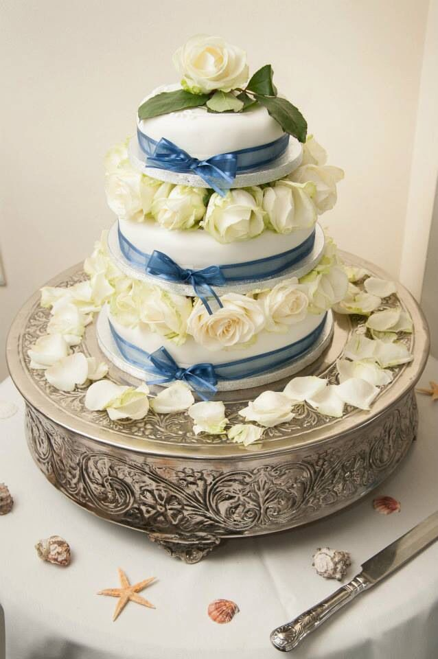 Wedding cake. Simple yet stunning!! You can easily make this at home! Choose three different sized iced ready made fruit cakes from your supermarket, then buy roses and rose petals from a supermarkets flower stall, then find cheap coloured bows which you tie to create a stunning wedding cake for minimum price!