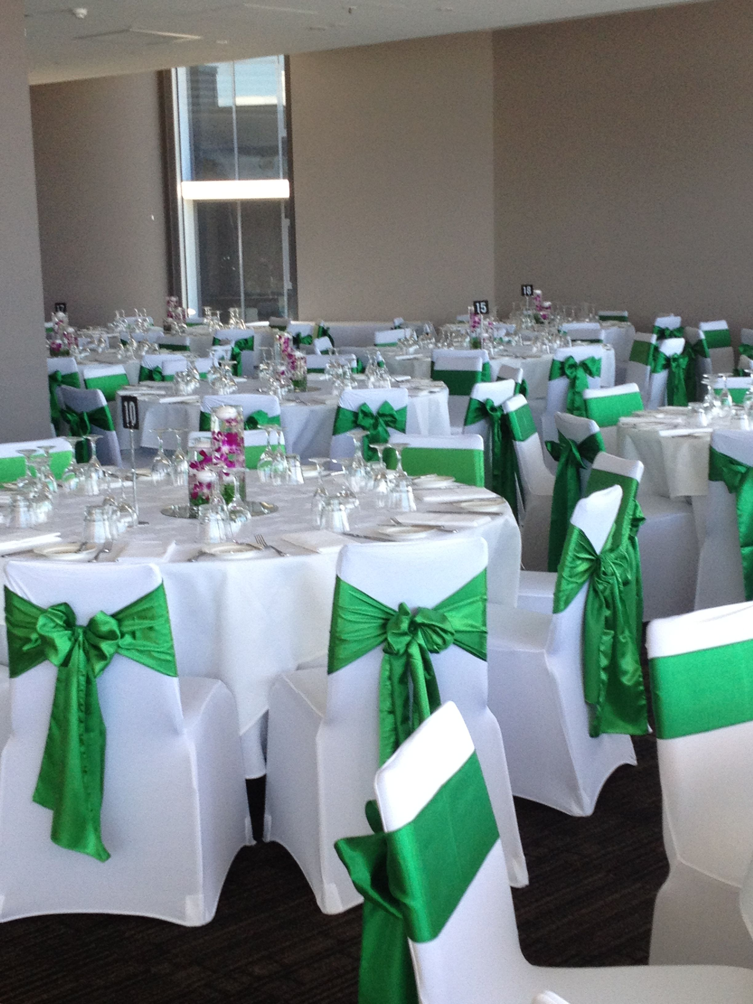 White Lycra Chair Covers With Emerald Green Satin Sashes Setup By