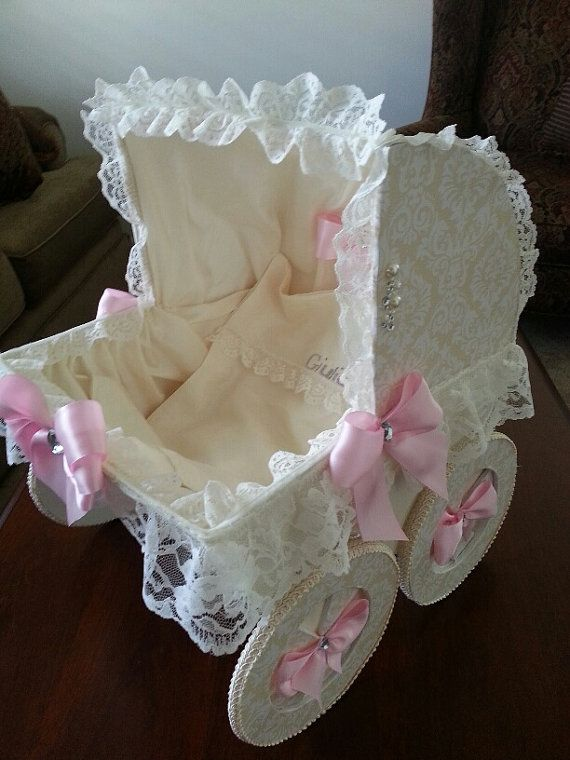 The Joycelyn 18 inch baby carriage centerpiece is larger than her 1 inch sister and will look perfect at an entry way or as the main centerpiece at your event. Perfect for holding gift cards and even sturdy enough to hold little story books. Its constructed of carolina board and foam board. The paper is a pretty polka dot pink. The carriage is trimmed in lace on the outside and a satin material lines the inside. A personalized blanket is also included.  USE: Purchase this carriage as a…