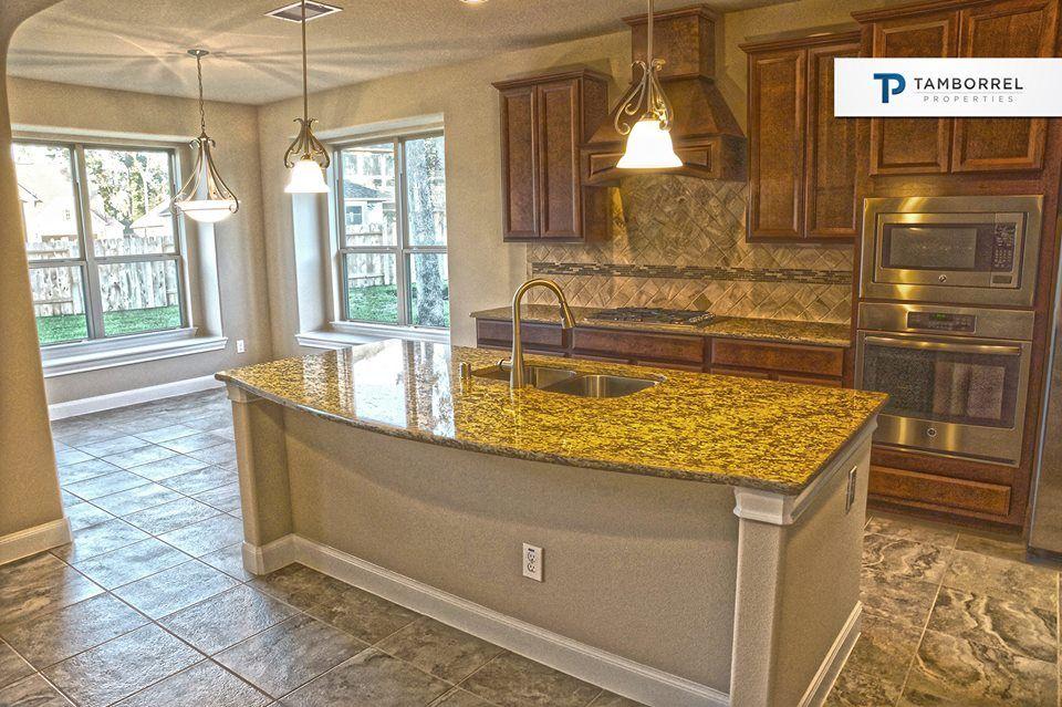 La cocina tiene encimeras de granito, azulejos y gabinetes de madera ...