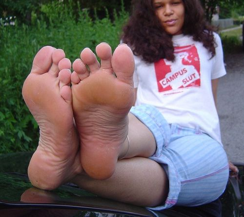 Bare soles resting on the windshield