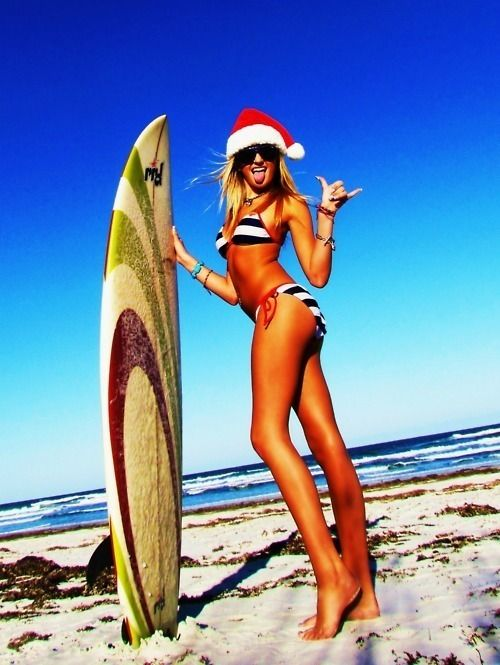 a18131107b42d Surfer girl sticking her tongue out in bikini and santa hat on the beach  with her surfboard.i should do this one year.