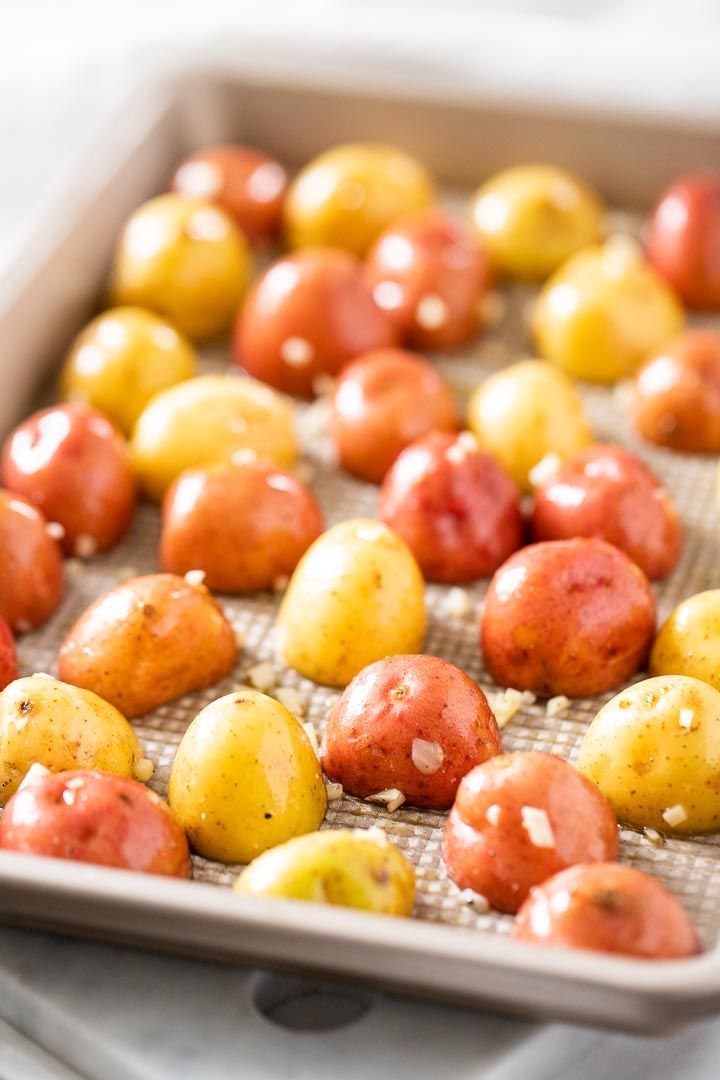 Simple Oven Roasted Potatoes made with Garlic and Parsley make an easy and delicious side dish that only requires a few minutes of prep and goes with so many meals! Whip up these crispy and golden roasted baby potatoes for a dinner that the whole family will love. #roastedpotatoes #ovenroastedpotatoes #sidedish #potatoes #garlicroastedpotatoes #babypotatoes #sheetpanrecipes #sides #dinner #recipe