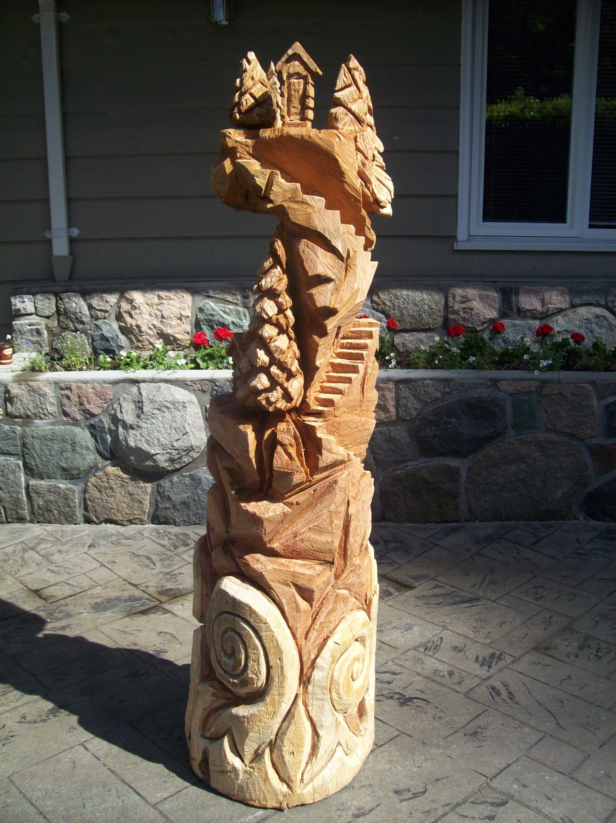 Cabin on cliff chainsaw carved from one western red cedar