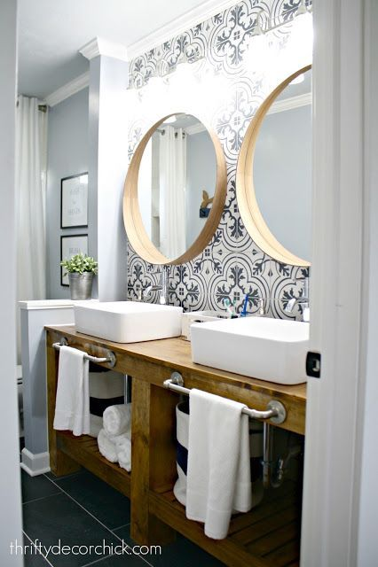Our modern farmhouse bathroom reveal complete with a diy wood vanity subway tile shower cement tile wall and round wood mirrors