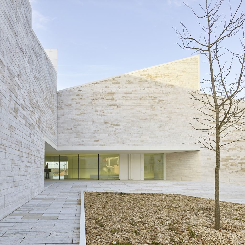 pale travertine walls frame cour et jardin cultural centre
