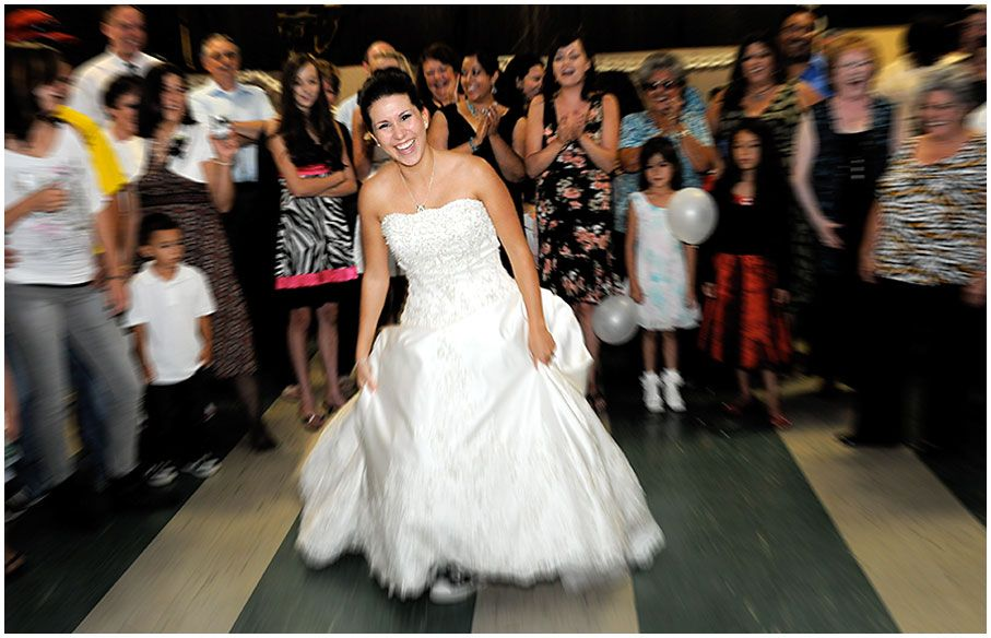 A happy bride dances in front of her family