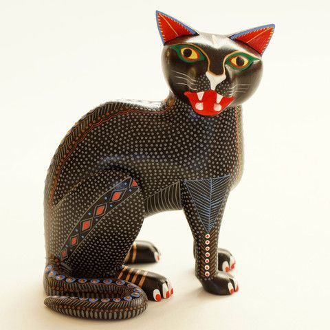 A beautiful black cat carved and painted by Rene Xuana of San Martin Tilcajete, Oaxaca. If you are familiar with the Xuana pieces, they are exceptionally well done both in the carving and the painting. This small black cat is a little more ferocious than most, baring his teeth to