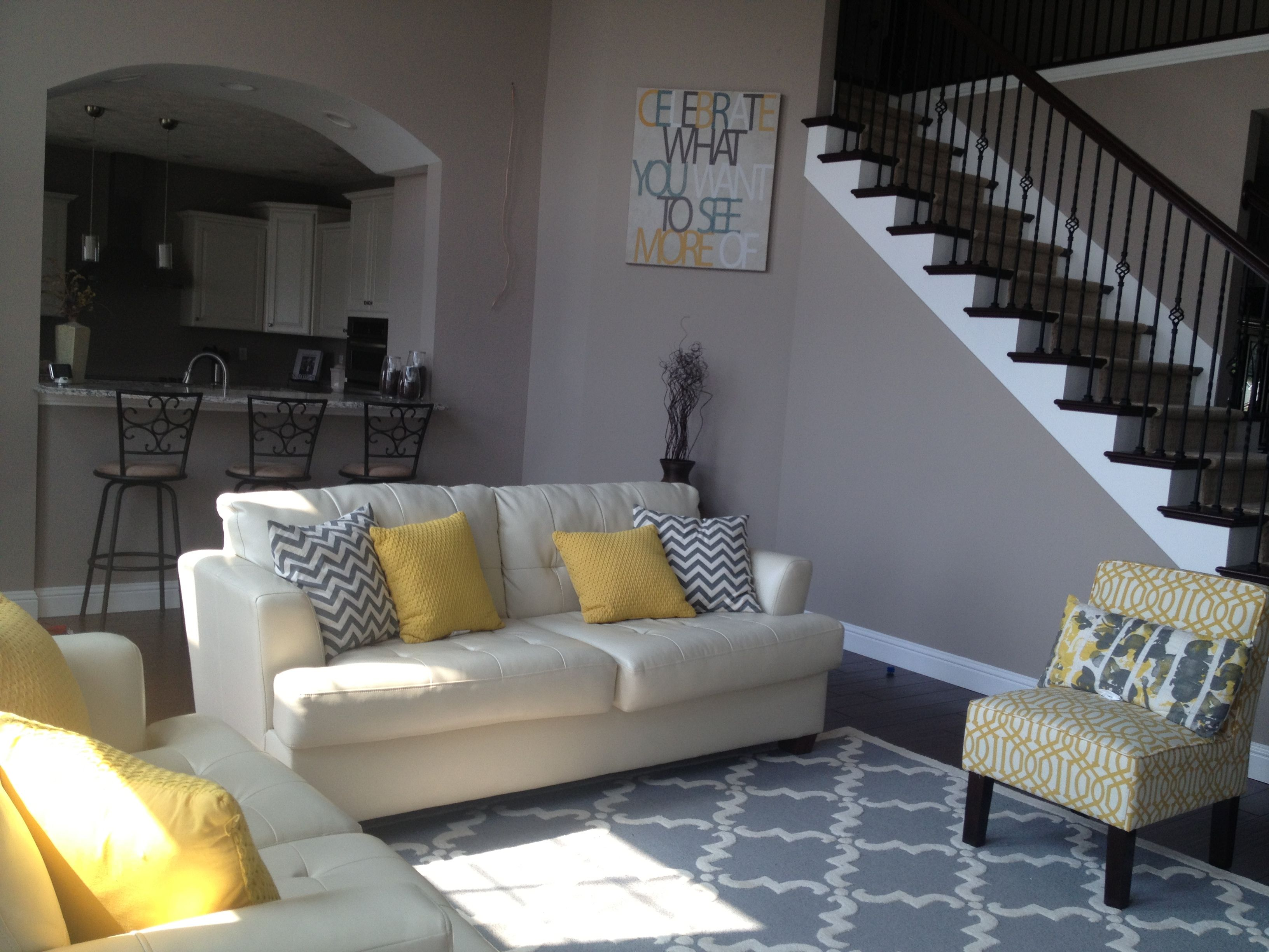 yellow and gray living room. trellis rug. chevron pillows. trellis