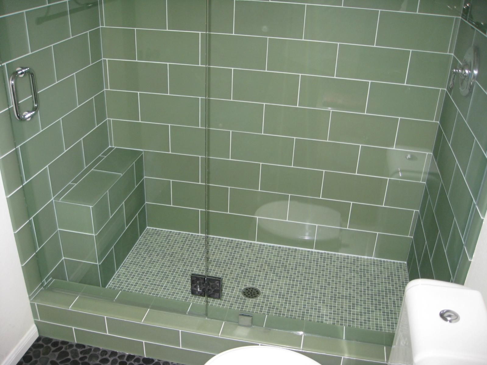pebble stone shower floor with subway tile and glass doors