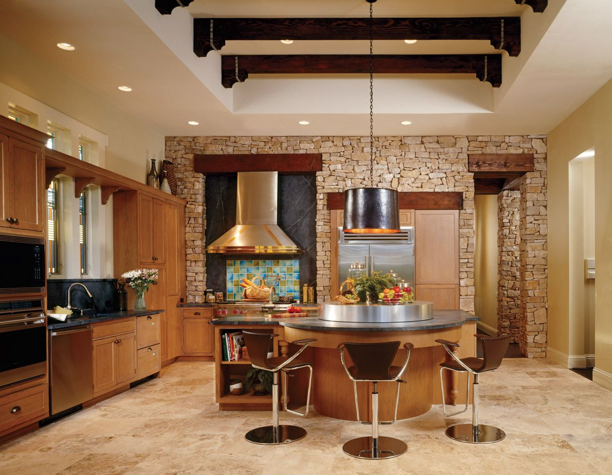 Glazed-oak Wood-Mode cabinetry lends strength and natural beauty to this kitchen, where appliances from Sub-Zero, Bosch, and Fisher & Paykel add gourmet touches. A copper drum light fixture suspends above a stainless-steel Lazy Susan, and a tile backsplash from Walker Zanger gives a hint of color.
