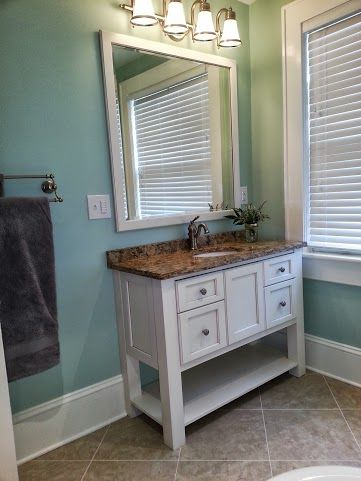 Bathroom Remodel: Table style cabinets and counter top sink with stone counter top. White wood cabinetry and framed standalone mirror with robin egg blue painted walls