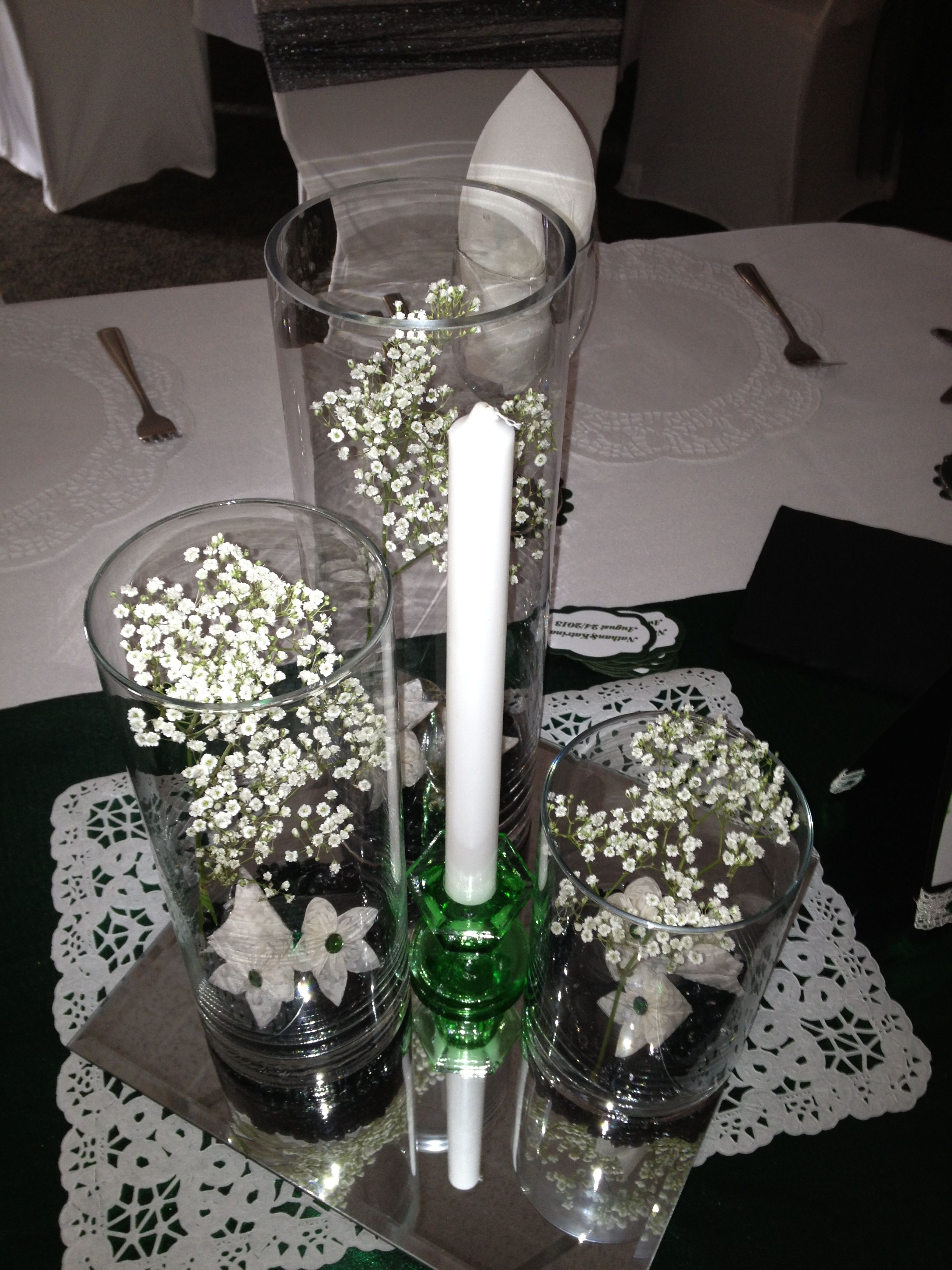 Centerpiece included tiered cylinder vases with black