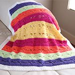 """This beautiful blanket features a dragonfly motif in colorful rainbow rows and a """"fluffy"""" white border. It makes a lovely gift for a new baby or a gorgeous lapg"""