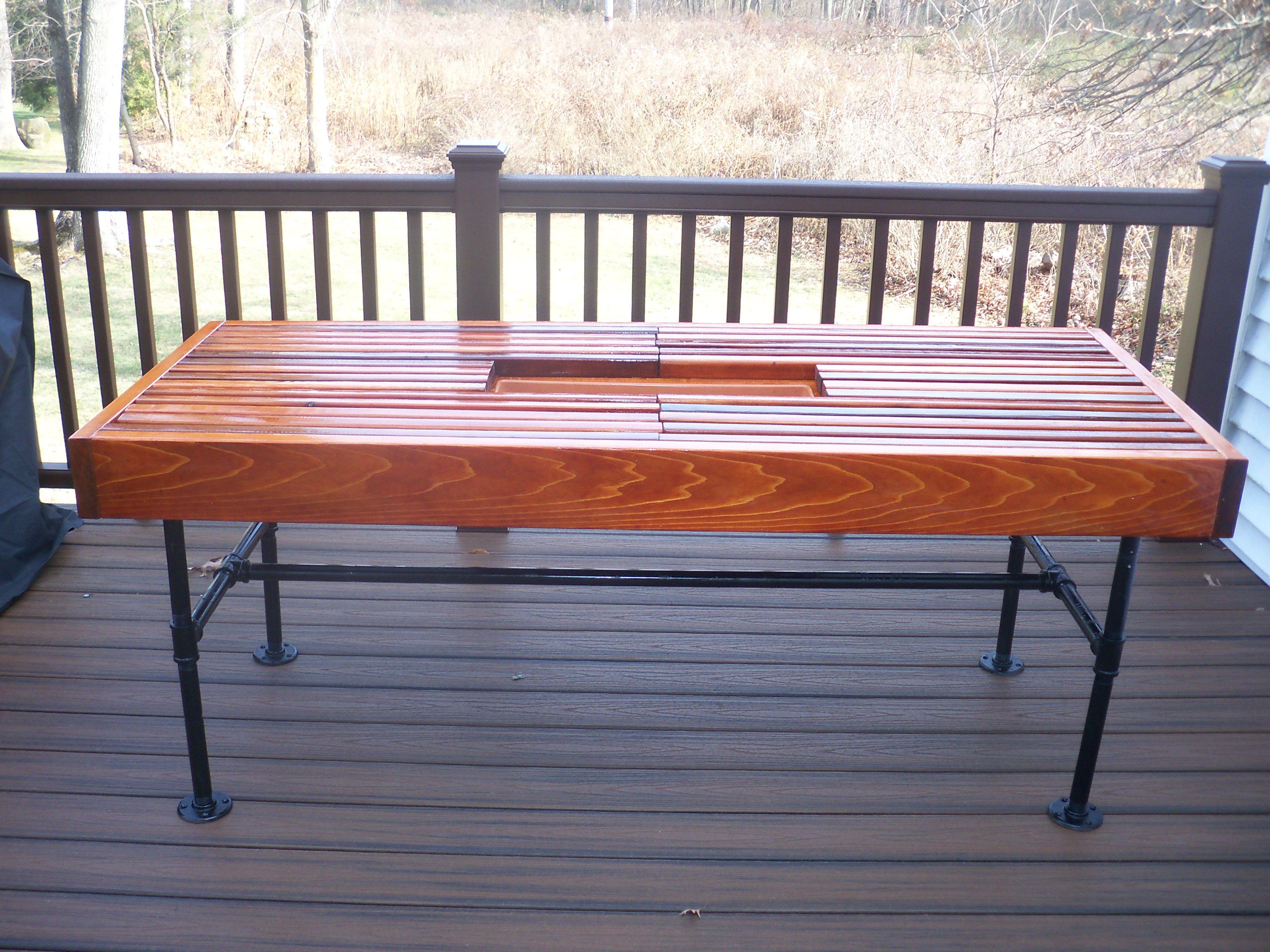 Cedar outdoor table with built-in wine & beer cooler with metal pipe legs.
