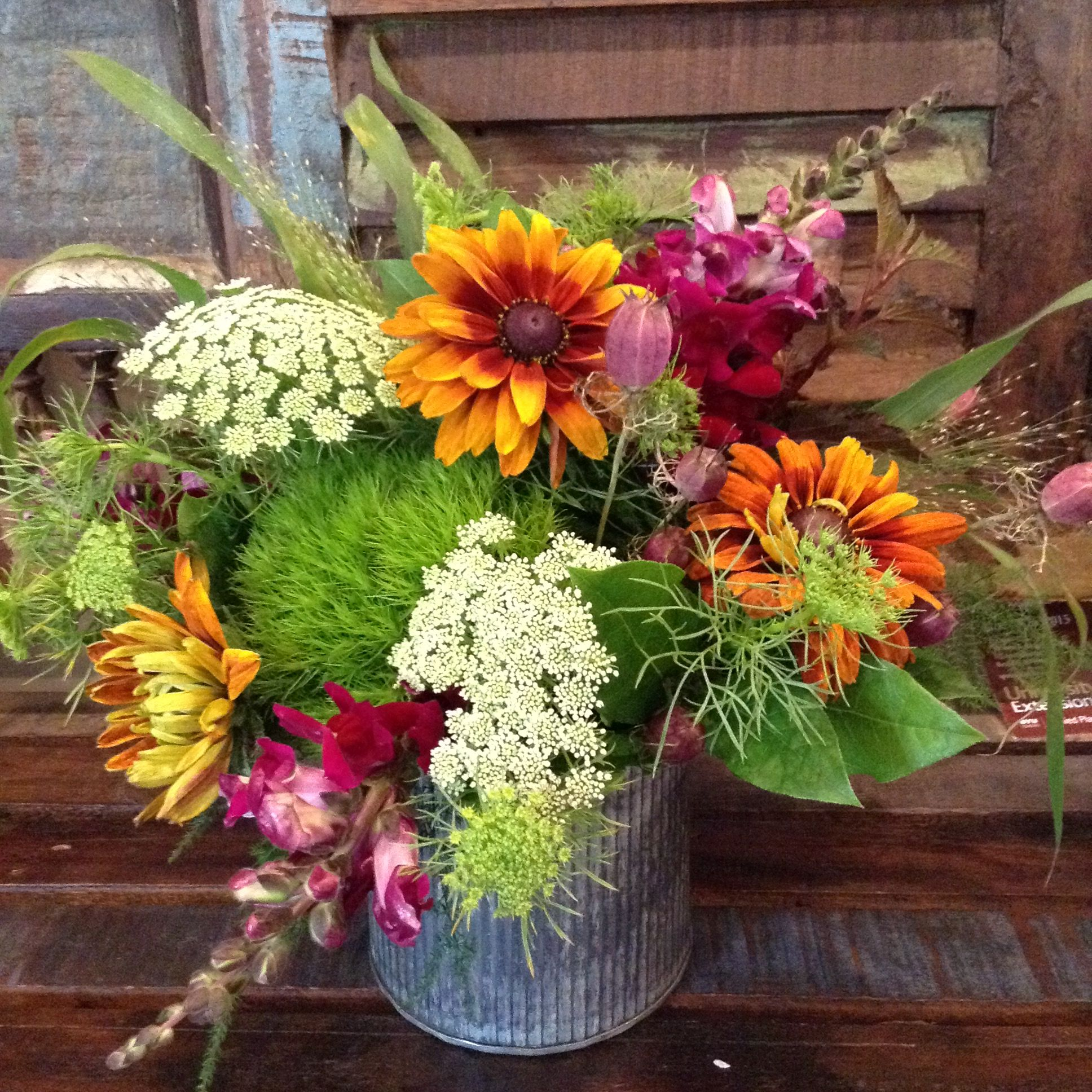locally grown chocolate susans, snaps and queen anne's lace add to the rustic charm of this table arrangement